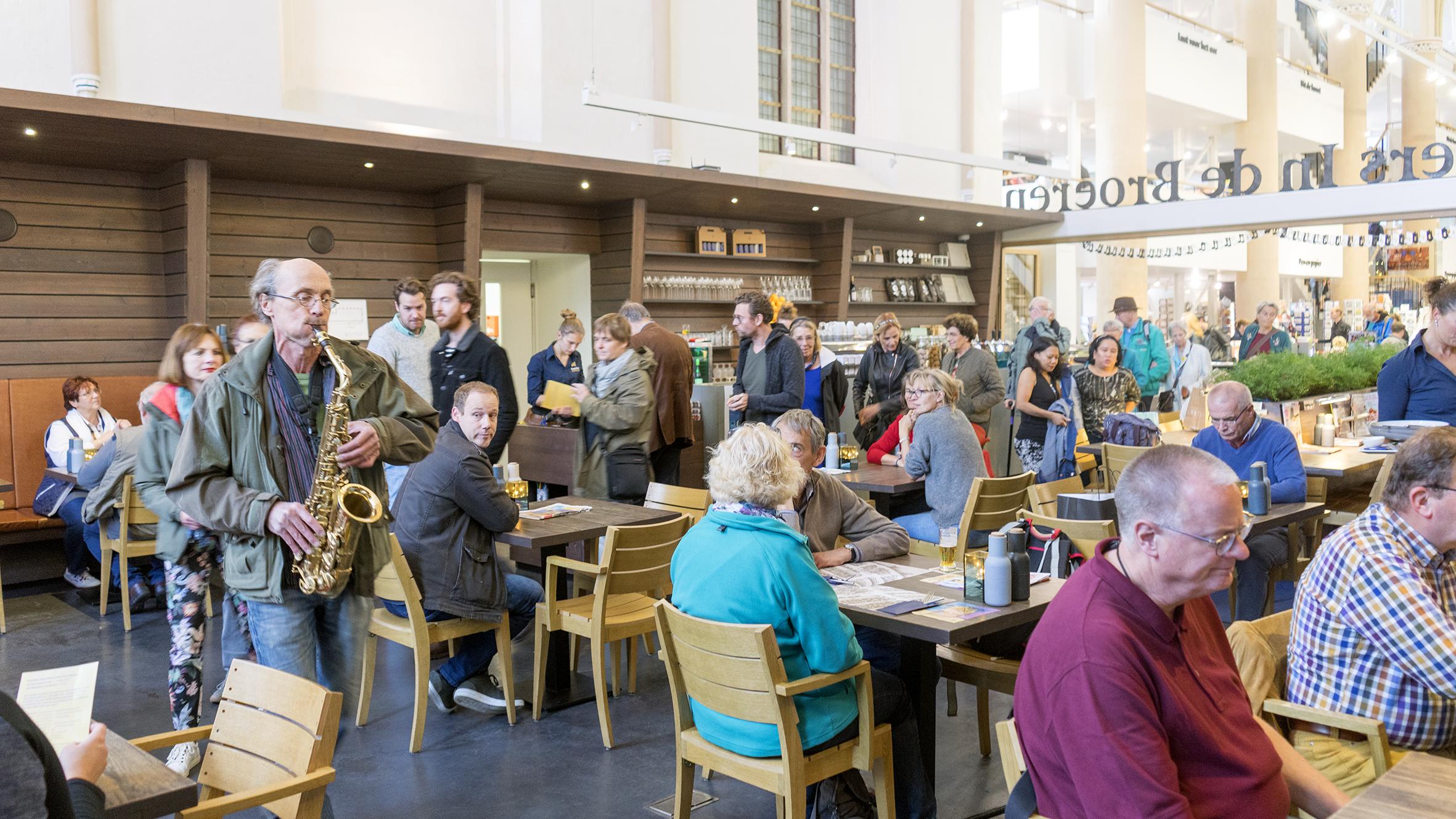 Man speelt saxofoon bij Waanders in de Broeren voor etend publiek