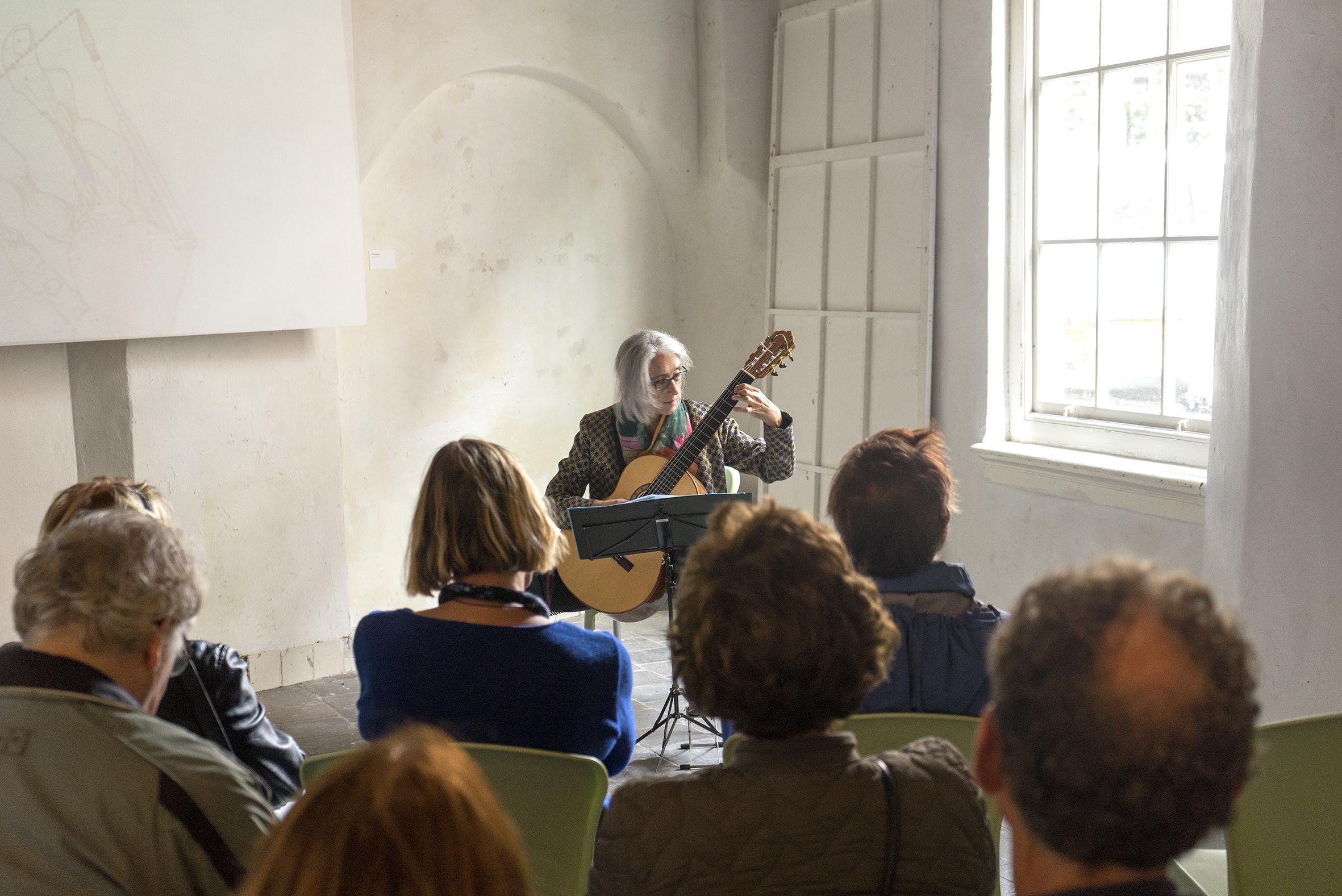 Vrouw speelt gitaar voor publiek